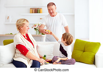 happy grandparents playing with grandson at home