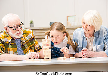 Happy grandparents with granddaughter playing jenga game together at home