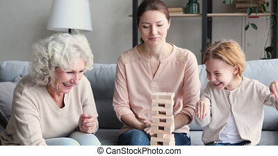 Happy granny and mommy supporting little child in build game...