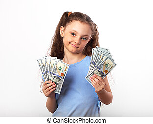 Happy grimacing doubt thinking kid girl holding money in the hands and looking on white background with empty copy space