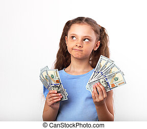 Happy grimacing doubt thinking kid girl holding money in the hands and looking up on white background with empty copy space
