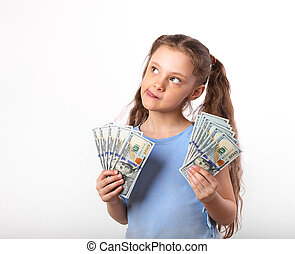 Happy grimacing fun thinking kid girl holding money in the hands and looking up on white background with empty copy space