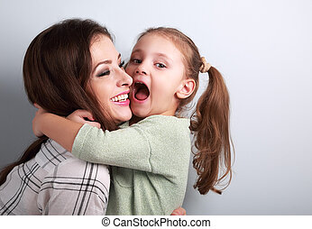 Happy grimacing kid wanting to biting her laughing mother in nose with fun face