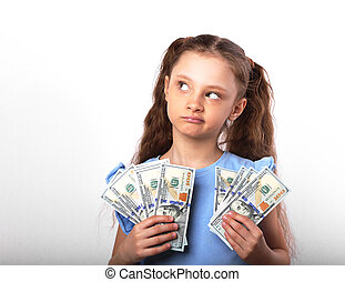 Happy grimacing thinking kid girl holding money in the hands and looking up on white background with empty copy space