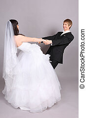 Happy groom and beautiful bride hold hands and circle in studio on gray background