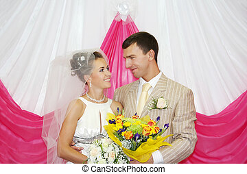 Happy groom and beautiful bride with flowers look at other