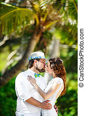 Happy groom and bride having fun in a tropical jungle under the palm tree. Wedding and honeymoon concept.