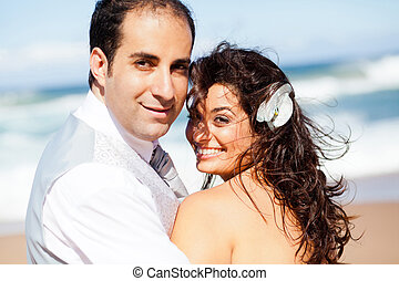happy groom and bride on beach