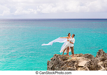 Happy groom and bride on the rock. Turquoise sea in the...