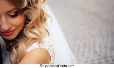 Happy groom and bride.  Very fresh and beautiful city at the shooting location. Bride blonde. Groom brunette. shot in slow motion  close up
