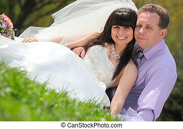 Happy groom and the bride sit on a grass