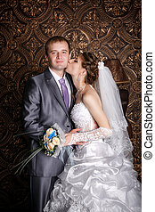 happy groom and the charming bride in studio on a brown background