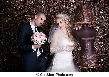 happy groom and the charming bride with a bouquet from roses in studio on a brown background