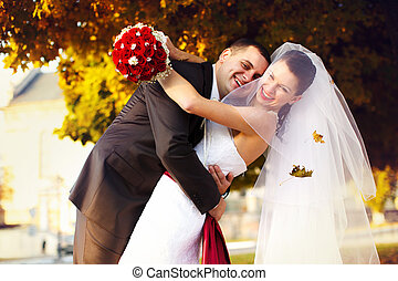Happy groom embraces a bride under autumn trees