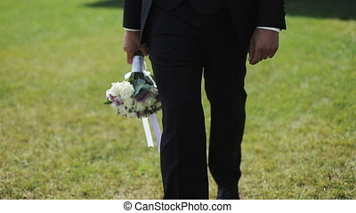Happy groom going to his wife with a bouquet in his hands