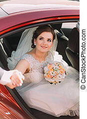 Happy groom helping his beautiful bride in white dress and with bouquet out of the wedding car.