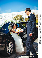 Happy groom helping his bride out of the wedding car.