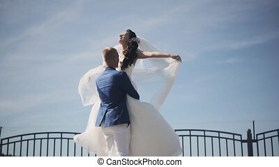 Happy groom hold on hands his bride in white wedding dress and turning around. Newlyweds enjoy sunny day. Slow motion.