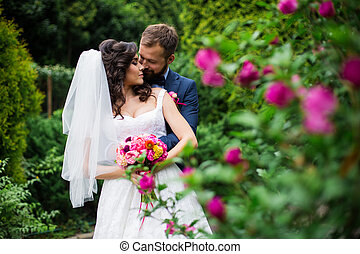 Happy groom hugging beautiful bride with bouquet from behind near flower bush