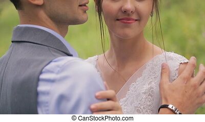 Happy groom tenderly embraces and kisses beautiful bride, close up.