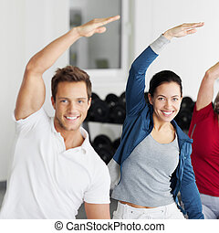 Happy Group Doing Stretching Exercise In Gym - Portrait of...