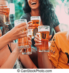 Happy group of best female friends drinking beer - Friendship concept with young female friends enjoying time and having genuine fun at outdoor nature ambient