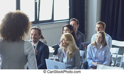Happy Group Of Business People Listening To Businesswoman Leading Presentation At Seminar Talking