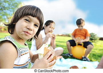 Happy group of children outdoor on meadow: eating and playing together