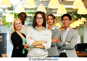 Happy group of co-workers standing in office