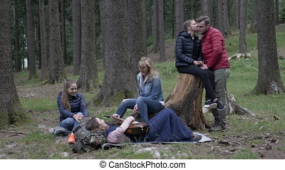 Happy group of friends camping in the woods enjoying nature...