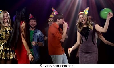 Happy group of friends dancing at a nightclub and throw balloons