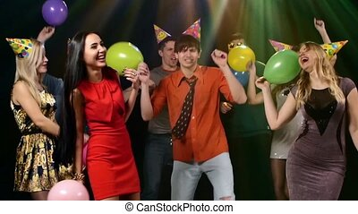 Happy group of friends dancing at a nightclub and throw balloons. Slow motion