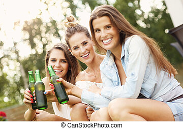 Happy group of friends drinking beer outdoors