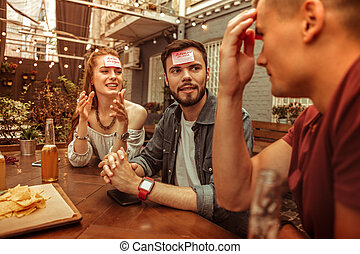 Happy group of friends playing hedbanz game at the bar.