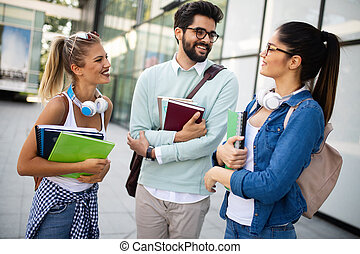 Happy group of friends studying and talking together at university