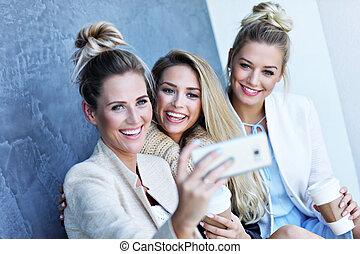 Happy group of friends taking selfie outside in autumn season