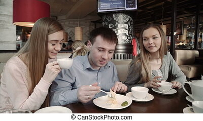 Happy group of friends Two young women and a man chatting, having drinks in city coffee shop cafe,