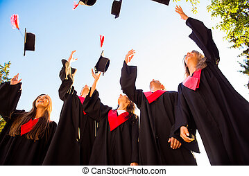 Happy group of graduated young students throwing hats in the air