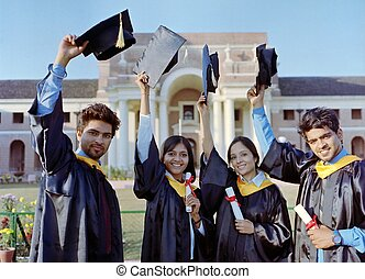 Happy group of Indian college students with arms up at their graduation ceremony.