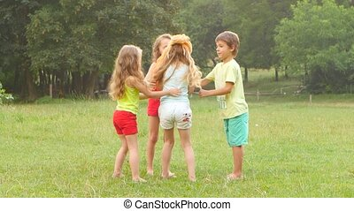 Happy group of little friends playing together outdoors in the summer