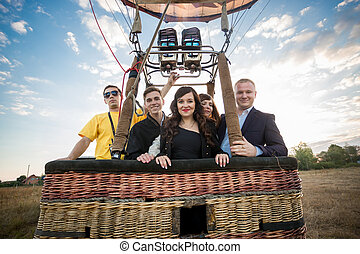 group of people posing in hot air balloon basket