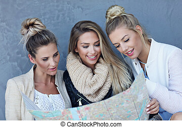 Happy group of tourists sitting outside with map in autumn season