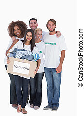 Happy group of volunteers holding donation box on white...