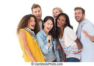 Happy group of young friends having fun doing karaoke on...