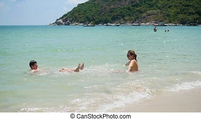 Happy guy and girl play makes splashes in the sea