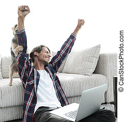 happy guy exults with his dog sitting near the sofa in the...