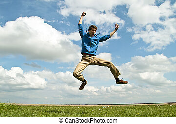 Happy guy jumping in the air on a beautiful day in ...