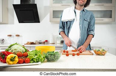 Happy guy making salad in cook room