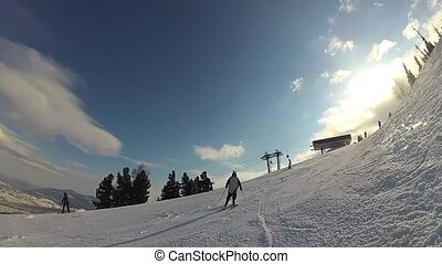 happy guy on a skiing sliding down the slope at sunny day