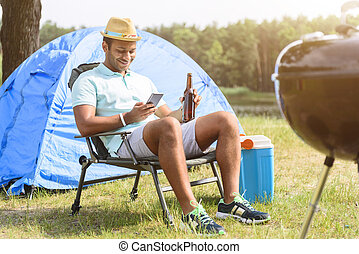 Happy guy relaxing in forest